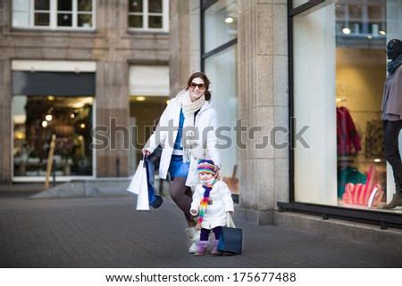 Young beautiful mother and her adorable toddler girl having fun at whiter sale shopping - stock photo