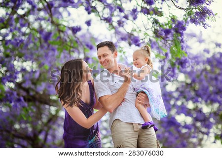 Young beautiful mother and her cute daughter love in blooming jacaranda garden - stock photo