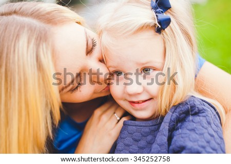 Young beautiful mother and her cute little daughter relaxing in park in summer. Both wear blue dresses. Both blonde. Mother kisses daughter in cheek while daughter shy and smile. Small bow in hair - stock photo