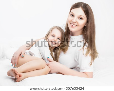 young beautiful mother  and her five years old daughter, in bed at home - stock photo
