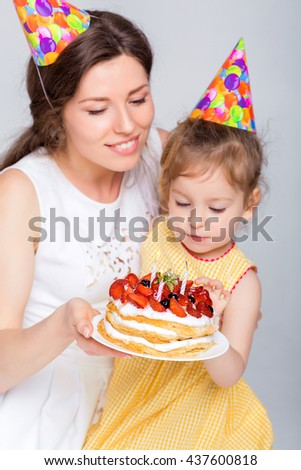 young beautiful mother and her little daughter are celebrating a birthday.cake with candles. mom and daughter are blowing on candles - stock photo