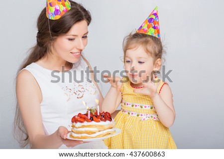 young beautiful mother and her little daughter are celebrating a birthday.cake with candles. mom and daughter are blowing on candles