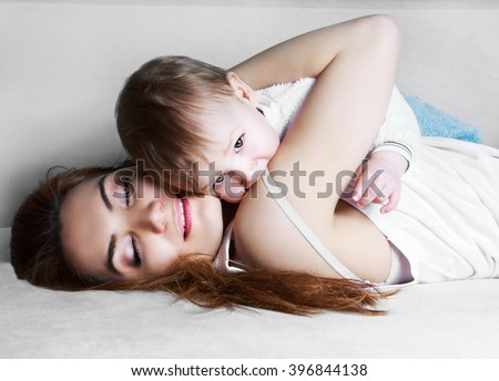 young beautiful mother and her one year old baby at home - stock photo
