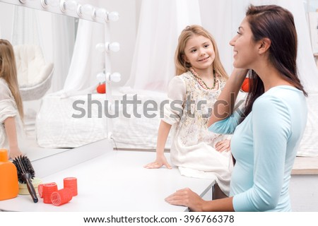Young beautiful mother and little daughter while applying makeup. Nice cozy bedroom. Daughter looking at mother and smiling - stock photo