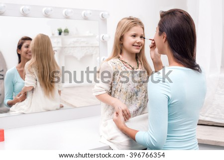 Young beautiful mother and little daughter while applying makeup. Nice cozy bedroom. Mother helping to paint daughter's eyelashes - stock photo