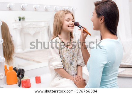 Young beautiful mother and little daughter while applying makeup. Nice cozy bedroom. Mother helping daughter to use brush for makeup - stock photo