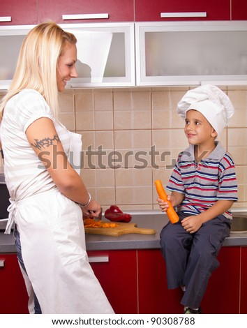 young beautiful mother and son in  kitchen - stock photo