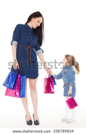 Young beautiful mother and sweet little daughter standing with shopping bags on a white background. Shopping family.