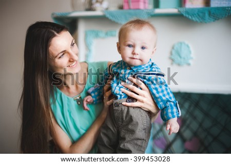 Young beautiful mother having fun holding her baby son; shot in shallow depth of field, focus on the boy's face - stock photo