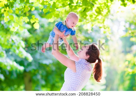 Young beautiful mother holding her baby son, adorable little boy, smiling and laughing during a walk in a beautiful sunny park on a hot summer day - stock photo