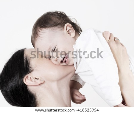 young beautiful mother holding her cute baby girl with isolated background - stock photo