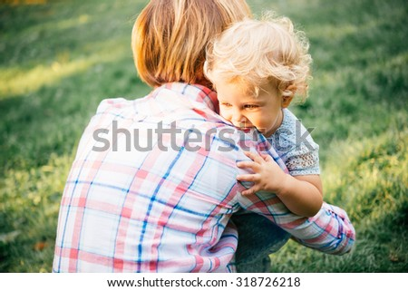 Young beautiful mother hugs her toddler blonde daughter during a walk outdoors