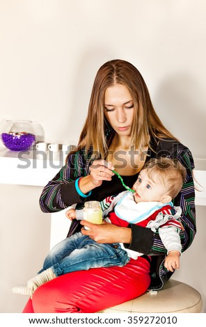 Young beautiful mother is feeding her cute  little boy with a puree in modern surrounding. - stock photo