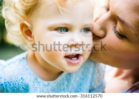 Young beautiful mother kisses her toddler blonde daughter during a walk outdoors - stock photo
