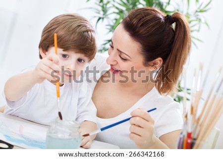 Young beautiful mother learn her child how to paint - stock photo