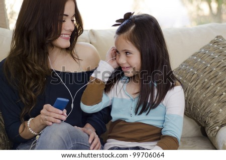 Young beautiful mother listening to music with her daughter