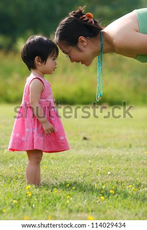Young beautiful mother looking at her daughter on spring field - stock photo
