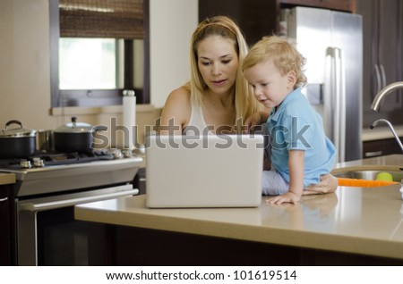 Young beautiful mother looking at something in her laptop with her cute son