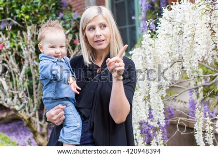 young beautiful mother showing something to her adorable toddler boy enjoying time together at the park at blooming springtime - stock photo