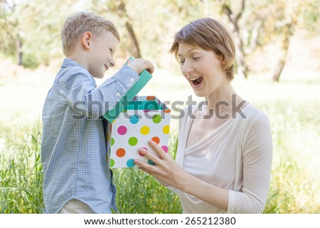 young beautiful mother surprised opening present from her little son at mother's day - stock photo