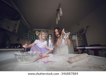 young beautiful mother teaches daughter prepare dough in the kitchen - stock photo