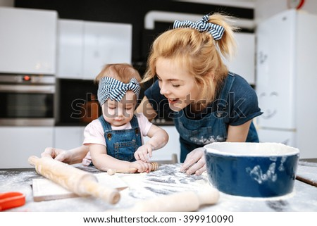 young beautiful mother teaches daughter prepare dough in the kitchen with fun - stock photo