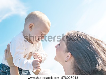 Young beautiful mother Tossing up baby boy on blue sky background in summer sunny day