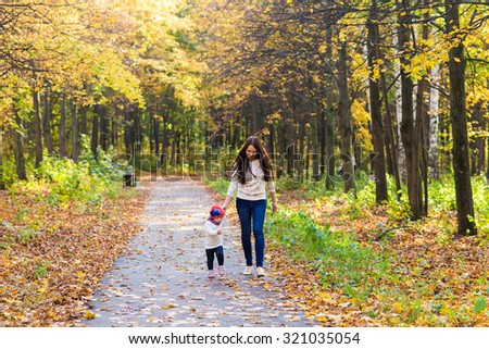 Young beautiful mother walking with her baby in an autumn park