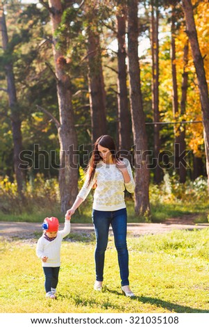 Young beautiful mother walking with her baby in an autumn park - stock photo