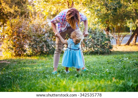 Young beautiful mother walks with her toddler blonde daughter in park - stock photo