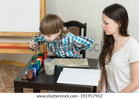 Young beautiful mother with boys son paint colors at home.