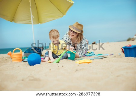 young beautiful mother with her little boy on the beach - stock photo