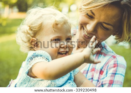 Young beautiful mother with her toddler blonde daughter during a walk outdoors. Toned image - stock photo