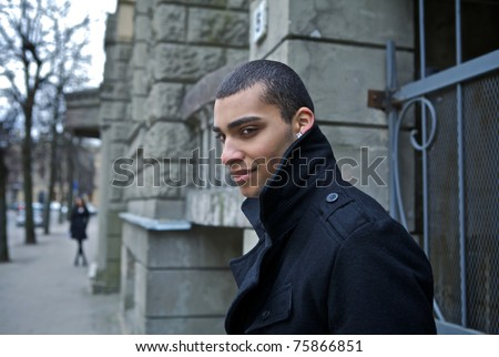 Young beautiful mulatto near old wold. Man and urban. Evening outdoor shoot. - stock photo