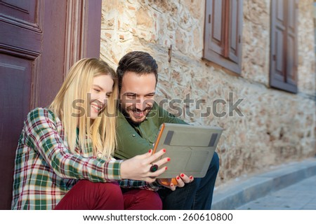 young beautiful multi ethnic couple sitting on the ground in city near old house and using digital tablet. - stock photo