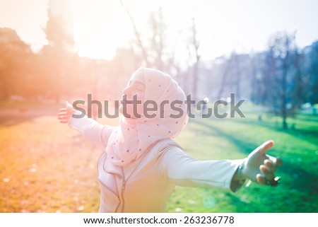 young beautiful muslim woman at the park in spring - stock photo