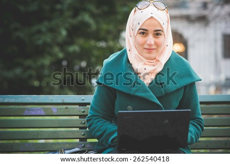 young beautiful muslim woman at the park in spring - filtered effect and intentional backlit  - stock photo