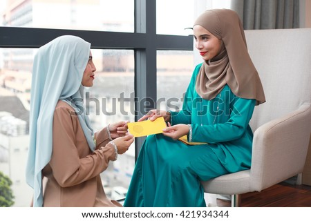 Young Beautiful Muslim Woman in head scarf with modern clothes received raya packets during hari raya aidilfitri festival - stock photo