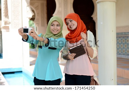 young beautiful muslim woman taking a self portrait with camera