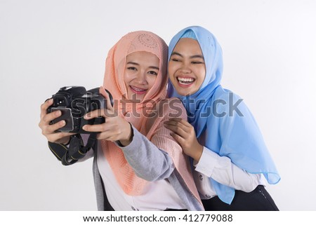 young beautiful muslim woman taking a self portrait with camera on a white background