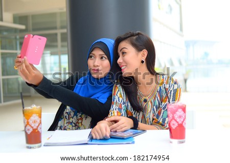 young beautiful muslim woman taking a self portrait with camera phone