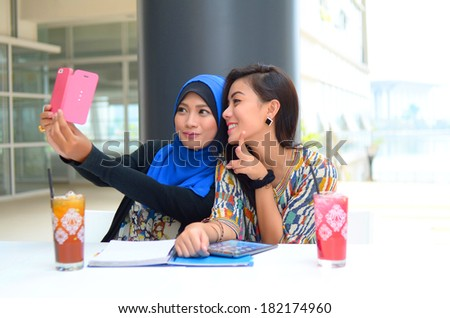 young beautiful muslim woman taking a self portrait with camera phone - stock photo