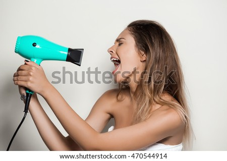 Young beautiful naked girl in towel singing with hairdryer.