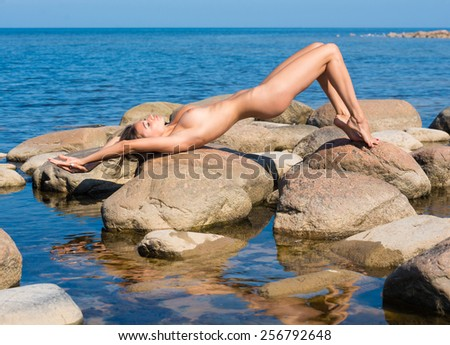 Young beautiful naked woman enjoying summer time on the beach - stock photo