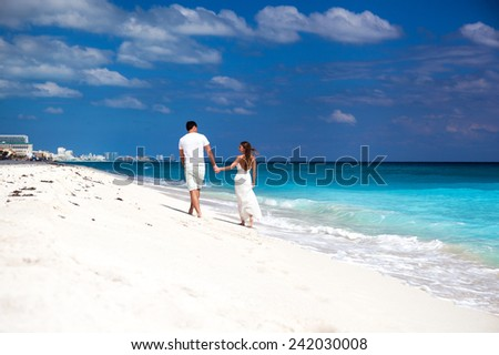 Young beautiful newlyweds in love holding hands and walking away on tropical sandy beach, back view