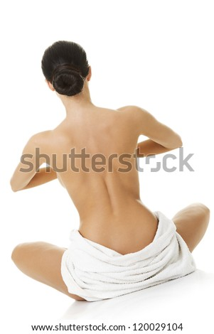 Young beautiful nude woman with towel practicing zoga , isolated on white