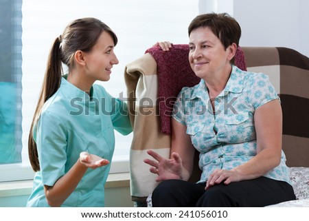 Young beautiful nurse talking with her older patient - stock photo