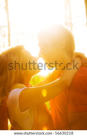 Young beautiful pair of lovers kissing at sunset