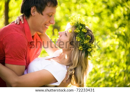 Young beautiful pair of lovers kissing in forest