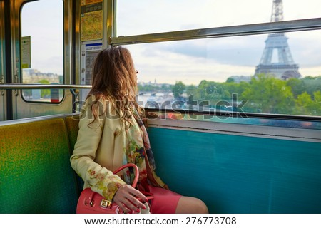 Young beautiful Parisian woman traveling in a subway train, sitting near the window and looking at the Eiffel tower - stock photo